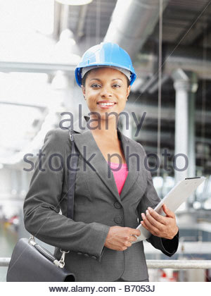 Businesswoman wearing hard-hat in warehouse - Stock Photo
