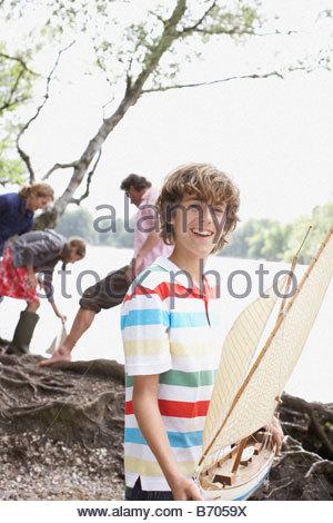 Boy holding toy sailboat near lake - Stock Photo