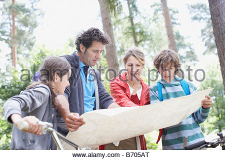 Family looking at map in woods - Stock Photo