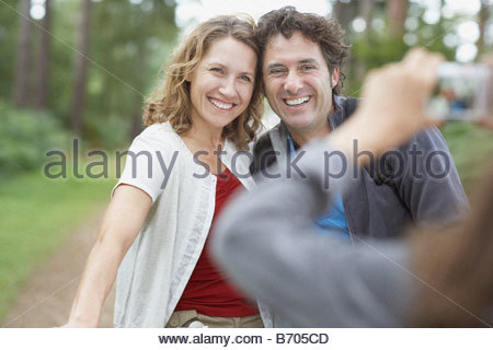 Girl taking photographs of parents in woods - Stock Photo