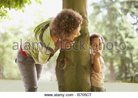 Mother playing hide and seek with son - Stock Photo