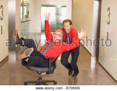 Businessman pushing co-worker in chair in corridor - Stock Photo