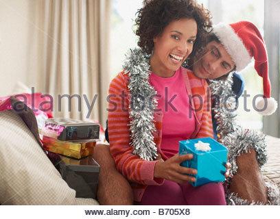Man watching wife open Christmas gift - Stock Photo