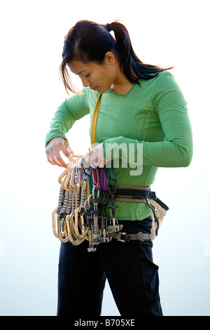 Attractive female climber adjusting a rack of quickdraws. - Stock Photo