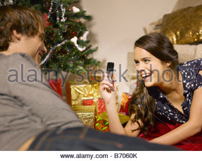 Couple taking pictures near Christmas tree - Stock Photo