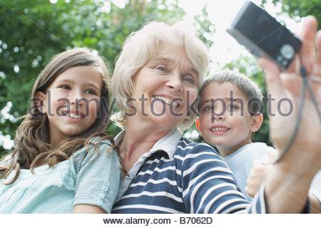 Grandmother taking self-portrait with grandchildren - Stock Photo