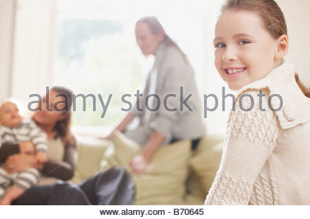 Girl smiling with family in background - Stock Photo