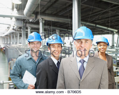 Businesspeople wearing hard-hats in factory - Stock Photo