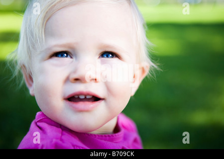 Portrait of a one year old baby girl in the park. - Stock Photo