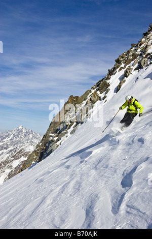 A young man skis untracked powder off-piste at the Stubai Ski Resort, near Innsbruck, Austria. - Stock Photo