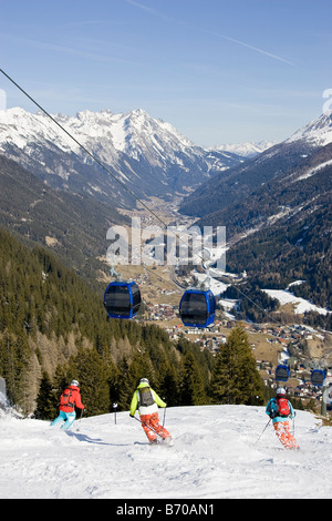 Three men ski down to the village of St. Anton am Arlberg, Austria. - Stock Photo