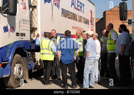 Professional HGV driver training instructor showing trainees around an HGV for daily checks and safety points - Stock Photo