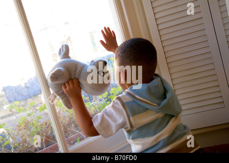 A young boy holding a teddy bear looking out of a window - Stock Photo