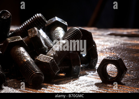 Random artistic pile of threaded bolts and a  hexagonal nut on a sheet steel, backlit, Nut, bolt, steel, sheet, - Stock Photo