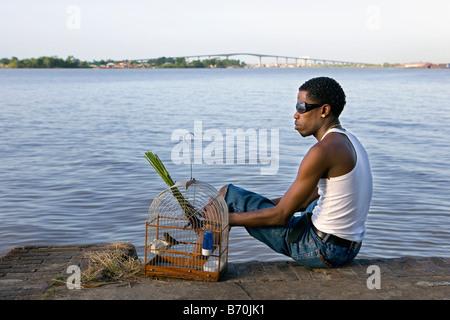 Suriname, Paramaribo. Creole man and singing picolet bird, eating rice-grass. Suriname river and Wijdenbosch bridge. - Stock Photo