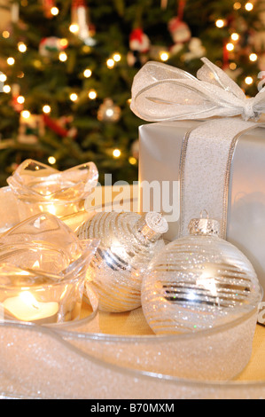 Silver Christmas ribbon, gift, ornaments & candles on table in front of lighted and decorated tree. - Stock Photo