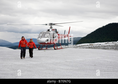 Helicopter tour guides walk from helicopter on top of Mendenhall Glacier near Juneau, Alaska - Stock Photo