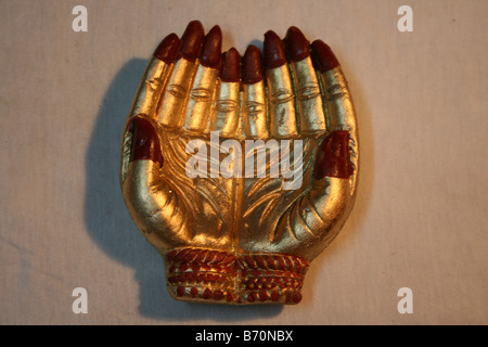 Manmade gold souvenir of two beautiful palms joined together as a sign of prayer or welcome and honor Diwali Festival - Stock Photo