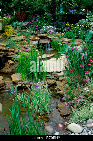 Attractive streamside planting with small waterfalls into a garden pond - Stock Photo