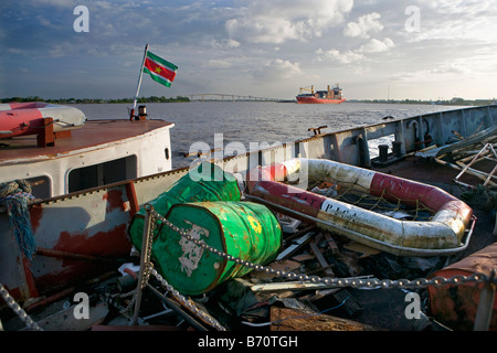 Suriname, Paramaribo. View from deserted ship in Suriname river, in background container ship and Wijdenbosch bridge. - Stock Photo
