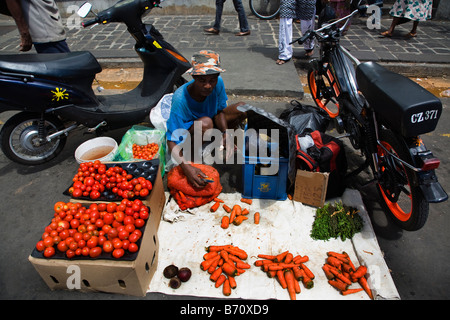 Market trader in the market in Port Louis Mauritius selling fruits and vegetables off the street - Stock Photo