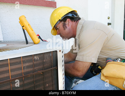 An air conditioning repairman working on a compressor unit - Stock Photo