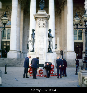 Men in suits looking at wreaths &  poppies on the memorial outside the Royal Exchange on Remembrance Day in City - Stock Photo