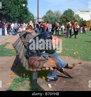 Tired tourists sit on a bench near people queuing for the London Eye Southbank England UK - Stock Photo