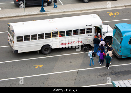 Tourists lined up to get on Juneau Tours tour bus at the cruise ship dock in Juneau, Alaska, USA - Stock Photo