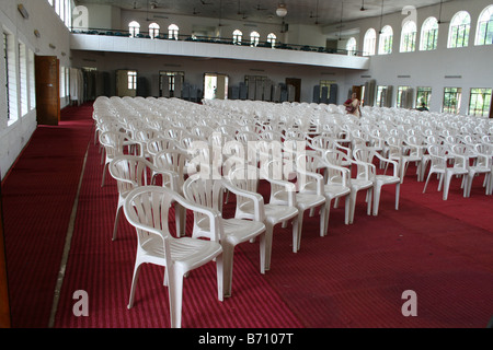 Large number of white color chairs on red carpet arranged for important public function or meeting in a huge hall - Stock Photo