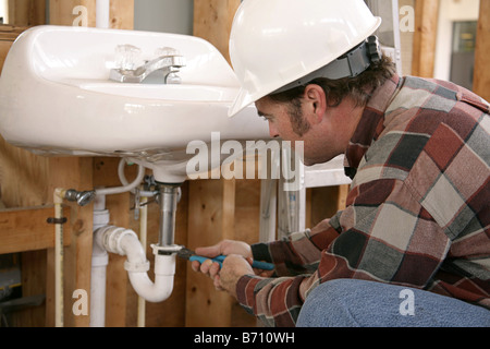 ... A Plumber In New Home Construction Installing Bathroom Fixtures Focus  On Plumber S Face   Stock