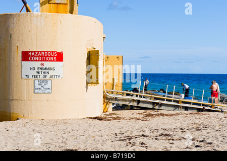 Palm Beach Shores , pumping station on jetty , no swimming & fishing signs ignored by swimmers & anglers or fishermen - Stock Photo