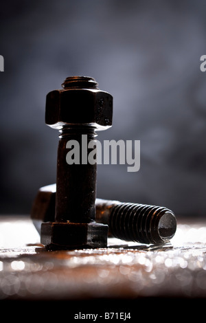 Random artistic pile of threaded bolts and a  hexagonal nut on a sheet steel, backlit. - Stock Photo