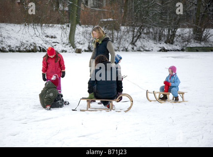 family resting on a frozen lake with sleighs - Stock Photo