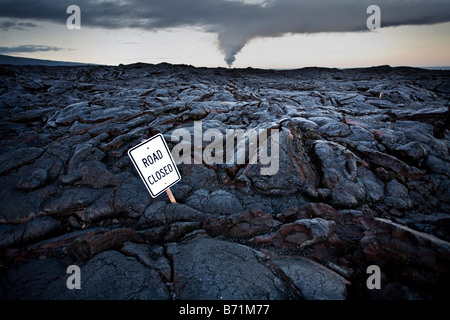 Road sign on road covered in lava with steam clouds from ocean entry in background, Kilauea volcano, Big Island, - Stock Photo