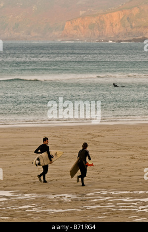 Two surfers running towards the sea at Sennen in Cornwall. - Stock Photo