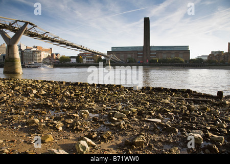 View of the Millennium Bridge and Tate Modern opposite from the Thames foreshore at low tide London England - Stock Photo