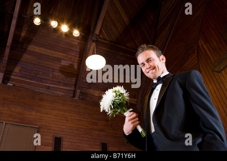Young groom holding floral bouquet in wooden church - Stock Photo
