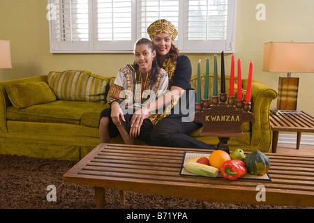 Happy African American mother and daughter celebrating Kwanzaa at home - Stock Photo