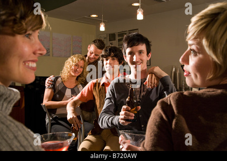 Affectionate young friends hanging out and drinking at restaurant together - Stock Photo