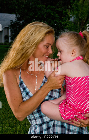 Mother holding toddler with down syndrome in backyard - Stock Photo