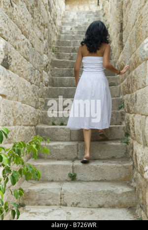 Woman in white dress climbing the stairs - Stock Photo
