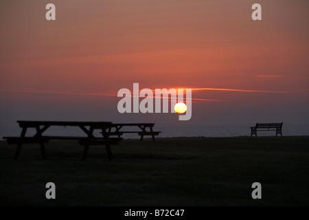 warm winter sunrise over picnic area on the county down coast Northern Ireland UK - Stock Photo