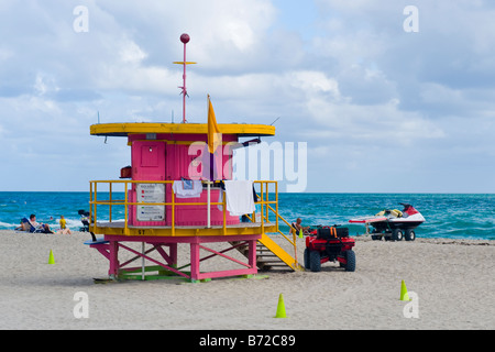 Miami South Beach lifeguard or lifesaver art deco pink green & yellow hut quad bike & water jet ski sand by blue - Stock Photo