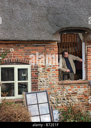 NEW WINDOW BEING FITTED TO OLD THATCHED COTTAGE HAPPISBURGH NORFOLK EAST ANGLIA ENGLAND UK - Stock Photo