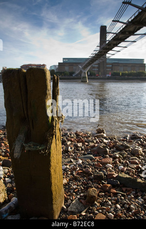 View of Tate Modern and the Thames foreshore at low tide from beneath the Millennium Bridge, London, England. - Stock Photo