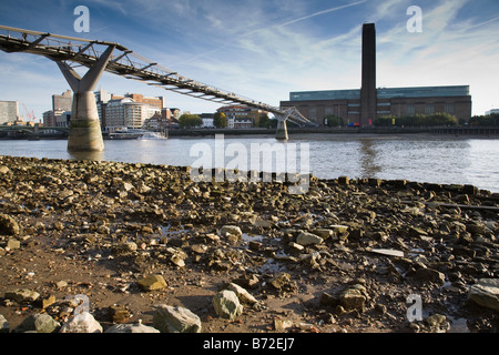 View of the Millennium Bridge and Tate Modern opposite from the Thames foreshore at low tide, London, England. - Stock Photo