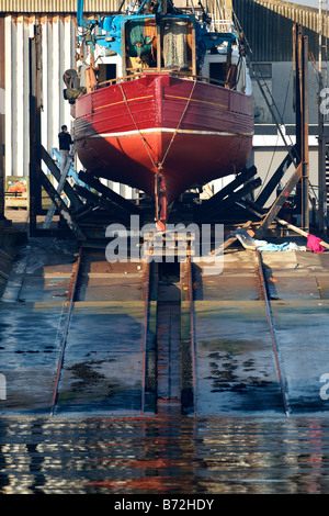 fishing boat in dry dock under repairs in portavogie county down Northern Ireland UK - Stock Photo