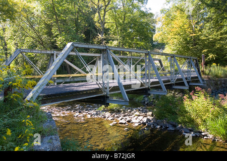 A lonely view of a country metal bridge with a flowing creek underneath the bridge. - Stock Photo