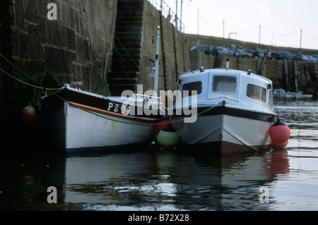 Two small day boats moored up in Mousehole harbour, Cornwall - Stock Photo
